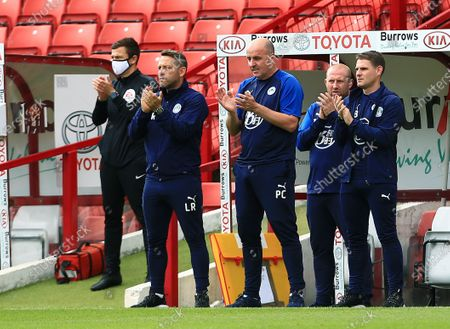 Wigan Athletic manager Paul Cook applauds ahead of the game
