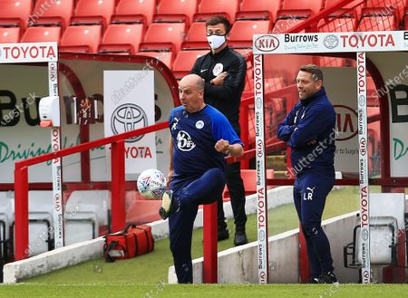 Wigan Athletic manager Paul Cook controls the match ball