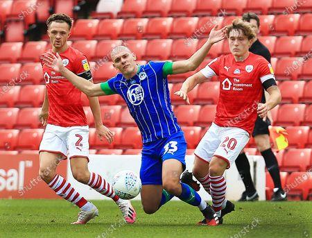 Kal Naismith of Wigan Athletic inbetween Jordan Williams and Callum Styles of Barnsley