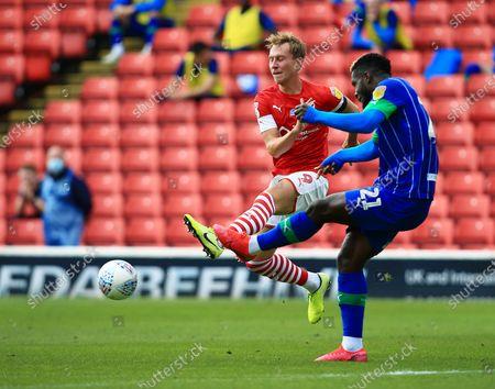Cauley Woodrow of Barnsley and Cedric Kipre of Wigan Athletic