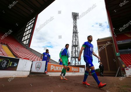 Wigan Athletic players make their way on to the pitch ahead of the game