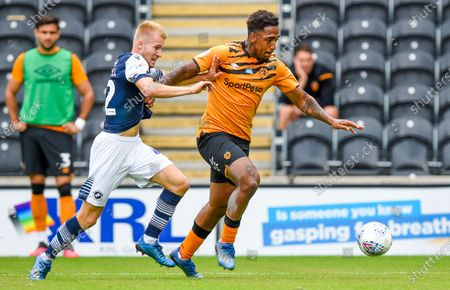 Stock Image of Mallik Wilks of Hull City forces his way through on goal as Billy Mitchell of Millwall tackles