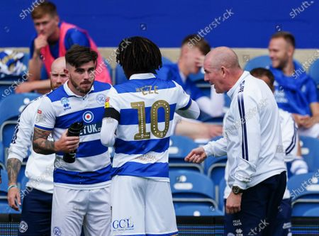 Ryan Manning of QPR talks to Eberechi Eze of QPR and Mark Warburton Manager of QPR during a break in play