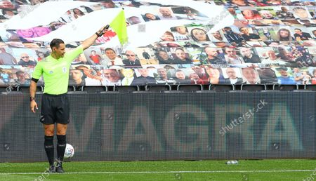 The assistant referee holds up his flag as the LED boards advertise Viagra