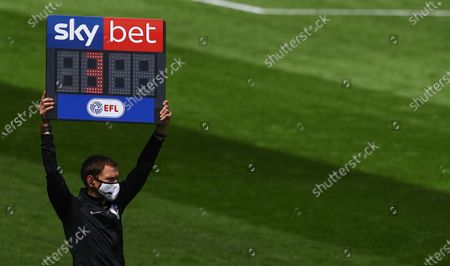 The fourth official holds up the Sky Bet added time board