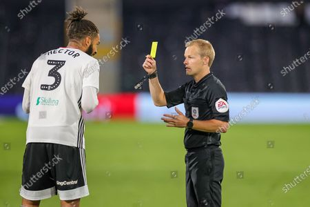 Referee Gavin Ward shows Fulham defender Michael Hector (3) a yellow card during the EFL Sky Bet Championship match between Fulham and Cardiff City at Craven Cottage, London