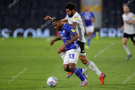 Fulham defender Cyrus Christie (22) challenges Cardiff City midfielder Junior Hoilett (33) during the EFL Sky Bet Championship match between Fulham and Cardiff City at Craven Cottage, London
