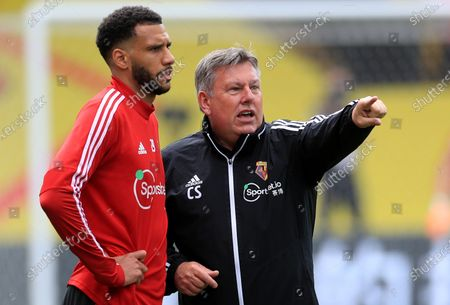 Watford assistant coach Craig Shakespeare (R) talks to player Etienne Capoue during the warm-up before the English Premier League match between Watford and Newcastle United in Watford, Britain, 11 July 2020.