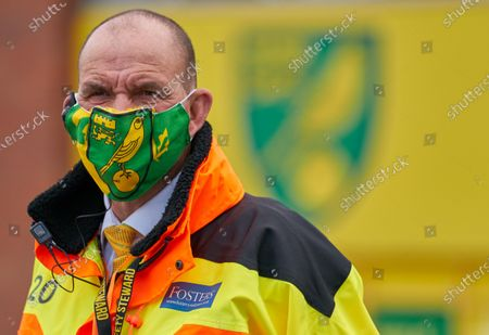 A Steward wearing a Norwich City branded face mask stands outside of Carrow Road. Norwich City play West Ham United in a Project Restart match behind closed doors.