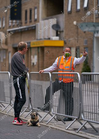 A steward wearing Norwich City branded PPE /  face mask, talks to a dog walker outside of Carrow Road. Norwich City play West Ham United in a Project Restart match behind closed doors.