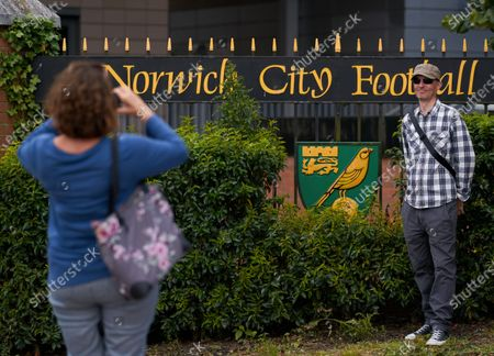 With no other fans in attendance, a couple takes an opportinuty to take pictures in front of the Norwich City gates at Carrow Road. Norwich City play West Ham United in a Project Restart match behind closed doors.