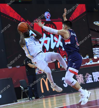Ty Lawson (L) of Fujian Sturgeons shoots the ball during a match between Fujian Sturgeons and Guangzhou Loong Lions at the 2019-2020 Chinese Basketball Association (CBA) league in Qingdao, east China's Shandong Province, July 11, 2020.