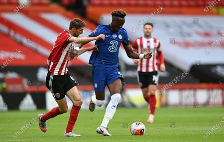 Chris Basham of Sheffield (L) in action against Tammy Abraham of Chelsea (C) during the English Premier League match between Sheffield United and Chelsea in Sheffield, Britain, 11 July 2020.