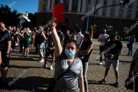 """A Bulgarian woman holds a red card during a protest in front of the Council of Ministers in Sofia, Bulgaria, 11 July 2020. Thousands of Bulgarians gathered in downtown Sofia for another day in support of President Rumen Radev, who called for """"cleansing of power confiscated by the mafia."""" The Prosecutor's office took over the presidency on 08 July 2020 searching the offices of the president's secretary for legal affairs and anti-corruption Plamen Uzunov and security and defense consultant Iliya Milushev, after which the two were arrested and charged with crimes to limit influence, among others, which led to protests in support of the president."""