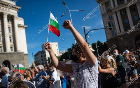 """Bulgarians shout slogans and hold the national flag during a protest in front of the Council of Ministers in Sofia, Bulgaria, 11 July 2020. Thousands of Bulgarians gathered in downtown Sofia for another day in support of President Rumen Radev, who called for """"cleansing of power confiscated by the mafia."""" The Prosecutor's office took over the presidency on 08 July 2020 searching the offices of the president's secretary for legal affairs and anti-corruption Plamen Uzunov and security and defense consultant Iliya Milushev, after which the two were arrested and charged with crimes to limit influence, among others, which led to protests in support of the president."""