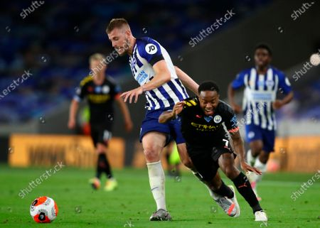 Brighton's Adam Webster (L) in action against Manchester City's Raheem Sterling (R) during the English Premier League match between Brighton & Hove Albion and Manchester City in Brighton, Britain, 11 July 2020.
