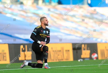 Photo libre de droits de Manchester City's Kyle Walker kneel down to make a stand against racism before the English Premier League match between Brighton & Hove Albion and Manchester City in Brighton, Britain, 11 July 2020.