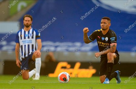 Manchester City's Gabriel Jesus (R) kneels down to make a stand against racism before the English Premier League match between Brighton & Hove Albion and Manchester City in Brighton, Britain, 11 July 2020.