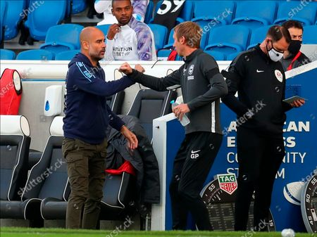 Manchester City manager Pep Guardiola (L) greets Brighton manager Graham Potter (R) the English Premier League match between Brighton & Hove Albion and Manchester City in Brighton, Britain, 11 July 2020.
