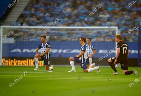 Players kneel down to make a stand against racism prior to the English Premier League match between Brighton & Hove Albion and Manchester City in Brighton, Britain, 11 July 2020.