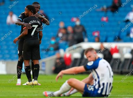 Manchester City's Raheem Sterling celebrates after scoring the 1-0 lead with Manchester City's Benjamin Mendy during the English Premier League match between Brighton & Hove Albion and Manchester City in Brighton, Britain, 11 July 2020.