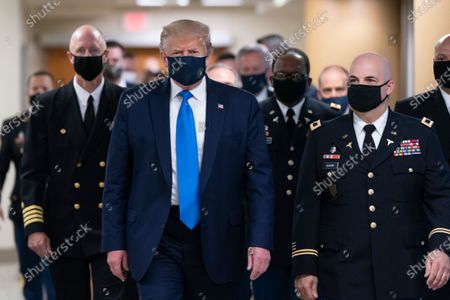 US President Donald J. Trump (C) wears a face mask as he arrives to visit with wounded military members and front line coronavirus healthcare workers at Walter Reed National Military Medical Center in Bethesda, Maryland, USA, 11 July 2020.