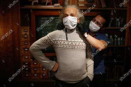 In order to raise awareness against the spread of the coronavirus, a worker at Madame Tussauds attraction in Istanbul, places a mask on the wax figure of Albert Einstein during a photo-op, . Turkish authorities have made the wearing of masks mandatory in most of the country to curb the spread of COVID-19 following an uptick in confirmed cases since the reopening of many businesses