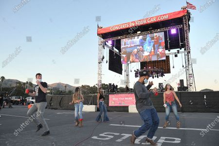 """Randy Hauser fans practice line dancing and social distancing at """"Concerts In Your Car,"""", at the Ventura County Fairgrounds in Ventura, Calif"""