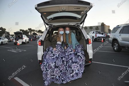 Hayley Cole, left, and Tessa Watkins both from Simi Valley, California, relax before the show at Concerts In Your Car, at the Ventura County Fairgrounds in Ventura, Calif