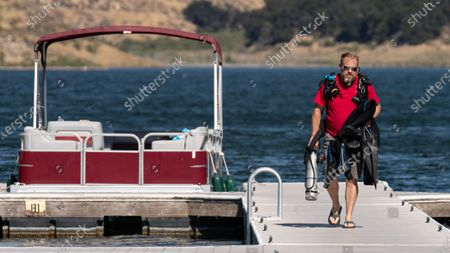 Diver Mike Miser packs his equipment after a full day of searching Lake Piru