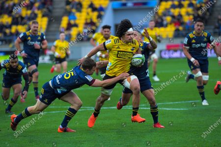 Michael Collins (left) of Hurricanes and Aaron Smith of Highlanders tackle Du'Plessis Kirifi of Hurricanes