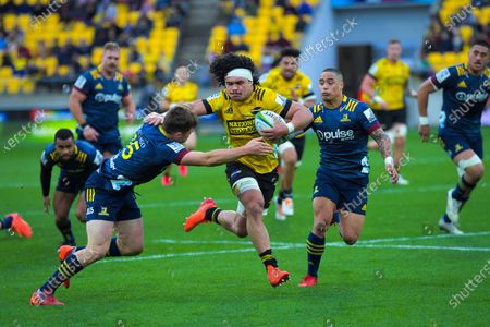 Michael Collins (left) and Aaron Smith of Highlanders tackle Du'Plessis Kirifi of Hurricanes