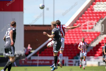Marc Roberts of Birmingham City (4) wins a header against Sam Vokes of Stoke City (9) during the EFL Sky Bet Championship match between Stoke City and Birmingham City at the Bet365 Stadium, Stoke-on-Trent