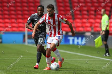 Tommy Smith of Stoke City (14) brings the ball away from Jérémie Bela of Birmingham City (11) during the EFL Sky Bet Championship match between Stoke City and Birmingham City at the Bet365 Stadium, Stoke-on-Trent