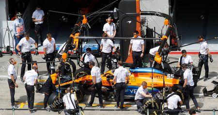 Mechanics prepare the car of Mclaren driver Carlos Sainz of Spain prior the Styrian Formula One Grand Prix race at the Red Bull Ring racetrack in Spielberg, Austria, Sunday, July 12, 2020. (Leonhard Foeger/Pool via AP)