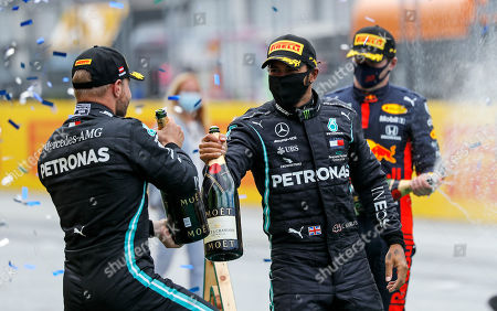 Mercedes driver Lewis Hamilton of Britain, center, celebrates his victory with second placed Mercedes driver Valtteri Bottas of Finland, left, after the Styrian Formula One Grand Prix race at the Red Bull Ring racetrack in Spielberg, Austria, Sunday, July 12, 2020. Third placed Red Bull driver Max Verstappen of the Netherlands on the right. (Leonhard Foeger/Pool via AP)