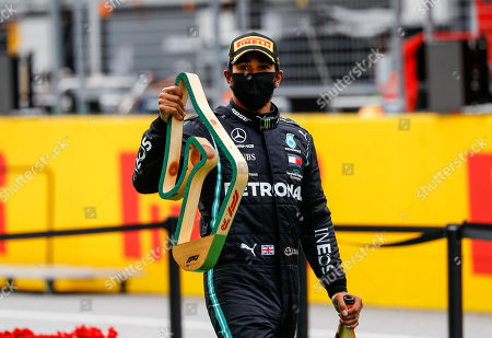 Mercedes driver Lewis Hamilton of Britain holds the trophy after winning the Styrian Formula One Grand Prix race at the Red Bull Ring racetrack in Spielberg, Austria, Sunday, July 12, 2020. (Leonhard Foeger/Pool via AP)