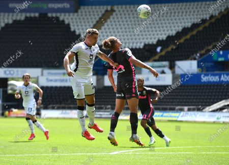 Erwin Mulder of Swansea City and Kalvin Phillips of Leeds United compete in the air.