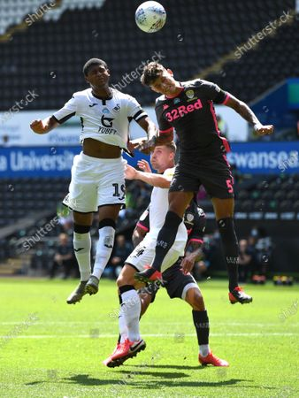 Rhian Brewster of Swansea City and Ben White of Leeds United compete in the air.