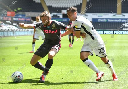 Stuart Dallas of Leeds United is tackled by Connor Roberts of Swansea City.