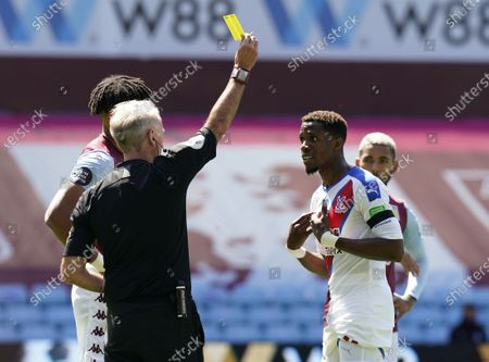 Wilfried Zaha (R) of Crystal Palace is booked by referee Martin Atkinson (L) during the English Premier League soccer match between Aston Villa and Crystal Palace in Birmingham, Britain, 12 July 2020.