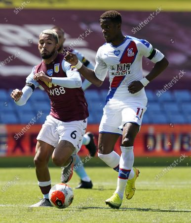 Douglas Luiz (L) of Aston Villa in action against Wilfried Zaha (R) of Crystal Palace during the English Premier League soccer match between Aston Villa and Crystal Palace in Birmingham, Britain, 12 July 2020.