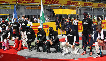 Drivers stand and knee against racism in the pit lane prior the Styrian Formula One Grand Prix race at the Red Bull Ring racetrack in Spielberg, Austria, Sunday, July 12, 2020. (Mark Thompson/Pool via AP)