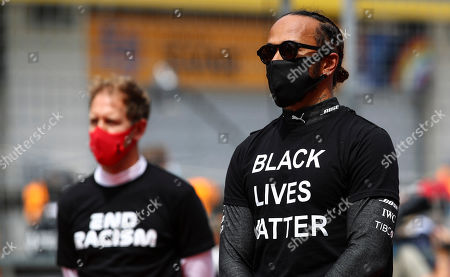 Ferrari driver Sebastian Vettel of Germany, left, and Mercedes driver Lewis Hamilton of Britain, wearing a Black Lives Matter shirt, stand against racism in the pit lane prior the Styrian Formula One Grand Prix race at the Red Bull Ring racetrack in Spielberg, Austria, Sunday, July 12, 2020. (Mark Thompson/Pool via AP)
