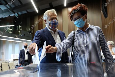 Stock Photo of Former president of Poland Aleksander Kwasniewski (L) with his wife Jolanta (R) casts his ballot at a polling station during presidential elections, in Warsaw, Poland, 12 July 2020.