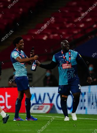 Sido Jombati and Adebayo Akinfenwa of Wycombe Wanderers celebrate promotion to the Championship after winning the EFL League 2 play off trophy by beating Oxford United 2-1 at Wembley