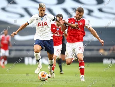 Erik Lamela (L) of Tottenham in action against Shkodran Mustafi (R) of Arsenal during the English Premier League soccer match between Tottenham Hotspur and Arsenal FC in London, Britain, 12 July 2020.