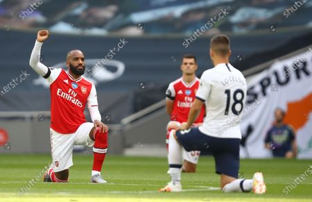 Alexandre Lacazette (L) of Arsenal takes a knee in support of the Black Lives Matter campaign ahead of the English Premier League soccer match between Tottenham Hotspur and Arsenal FC in London, Britain, 12 July 2020.