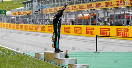 Mercedes driver Lewis Hamilton of Britain reacts alone on the podium after winning the Styrian Formula One Grand Prix race at the Red Bull Ring racetrack in Spielberg, Austria