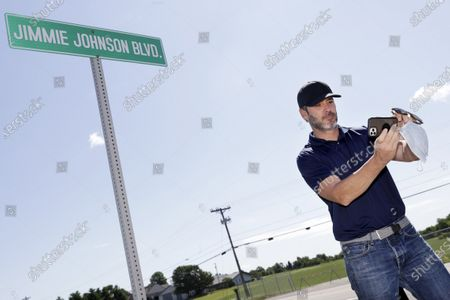 Driver Jimmie Johnson takes a selfie in front of the street sign bearing his name after it was unveiled outside Kentucky Speedway before a NASCAR Cup Series auto race, in Sparta, Ky